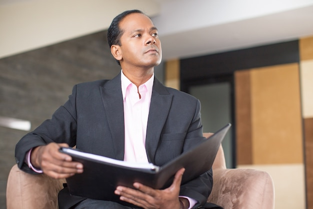 Thoughtful business man reviewing document