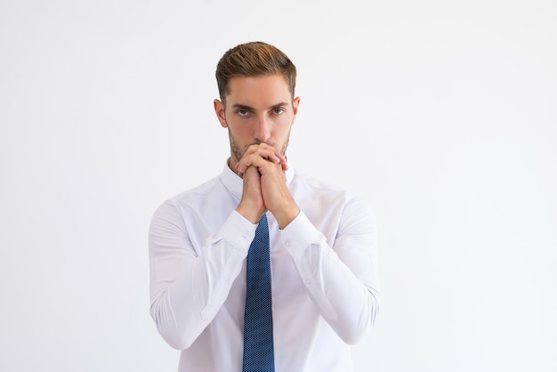 Thoughtful business man touching mouth with clenched hands