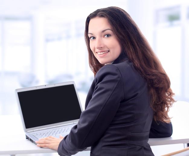 미소로 사무실에서 노트북에 대 한 사려 깊은 비즈니스 여자.