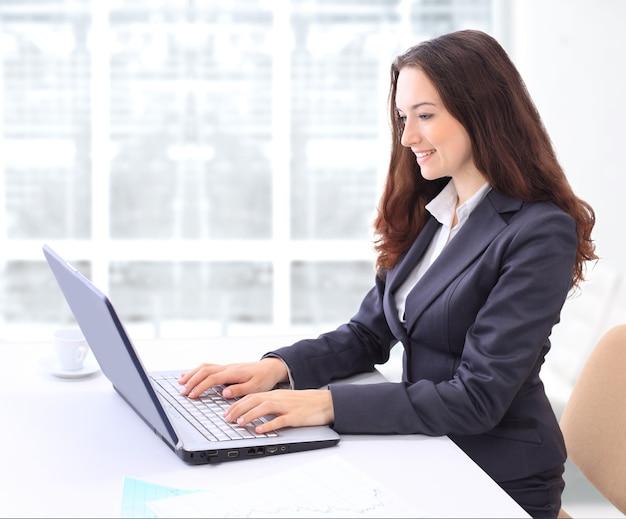 笑顔でノートパソコンのためのオフィスで思いやりのあるビジネスウーマン。