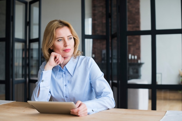 Thoughtful business woman using tablet at table