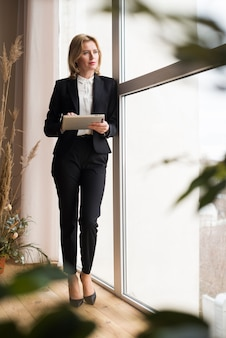 Thoughtful business woman using tablet
