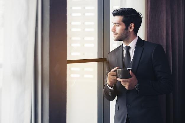 사려 깊은 사업가 마시는 커피, 창문을 통해보고
