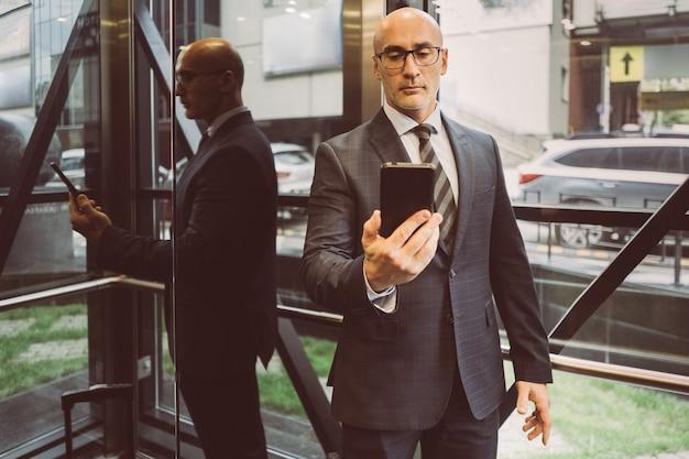 スーツを着た思いやりのあるビジネスマンがスマートフォンで情報を読んで彼の前にそれを保持します