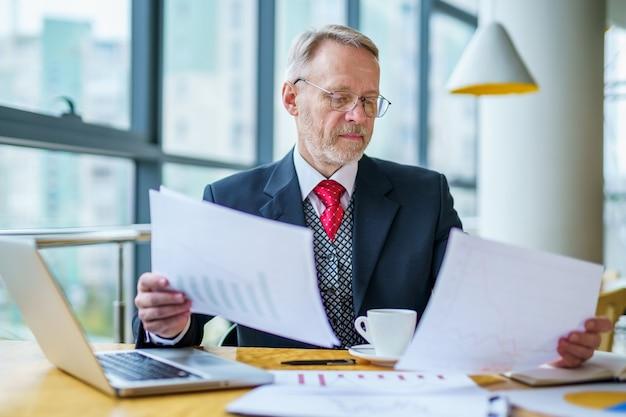 思いやりのあるビジネスマンが重要なビジネス ペーパーを読んでいる