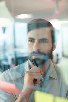 Вдумчивый бизнесмен, глядя на планы, написанные на стекле