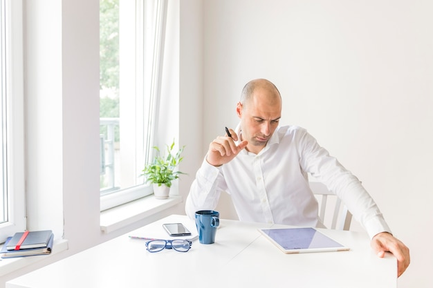 Thoughtful businessman looking at graphic digital tablet at workplace