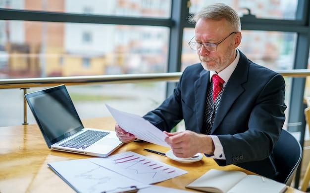 重要なビジネス ペーパーを読んでいる思いやりのあるビジネスマン