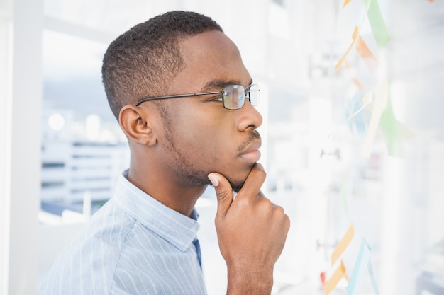 Thoughtful businessman reading sticky notes