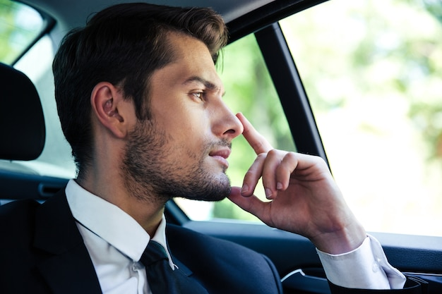 Thoughtful businessman riding in car