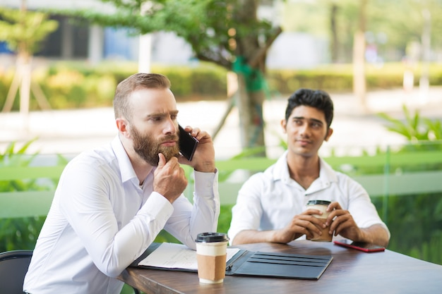 Thoughtful businessman rubbing beard while talking on phone