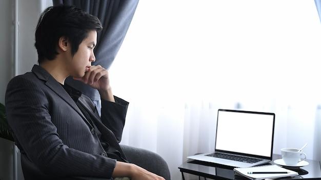 Вдумчивый бизнесмен, сидя на современном рабочем месте и глядя на портативный компьютер.