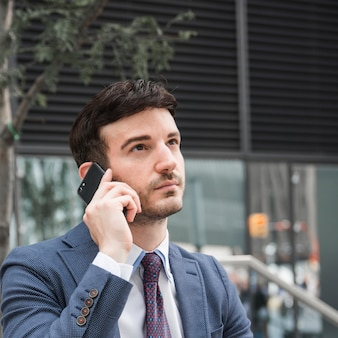 Thoughtful businessman speaking on smartphone