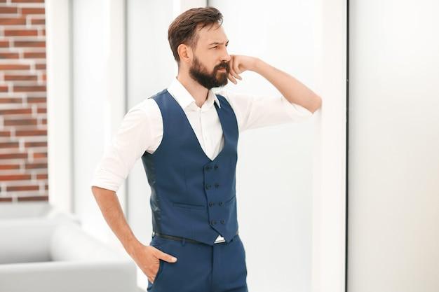 Вдумчивый бизнесмен, стоя возле окна офиса. бизнес-концепция