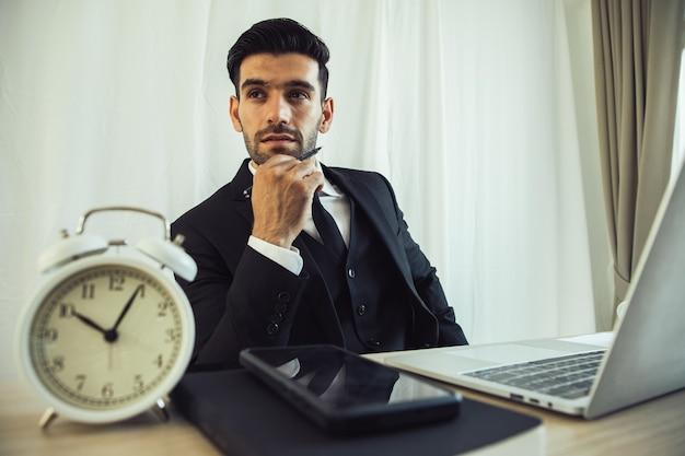 思いやりのあるビジネスマンは、目覚まし時計を使って職場のノートパソコンを見ながらオンライン プロジェクトを考える