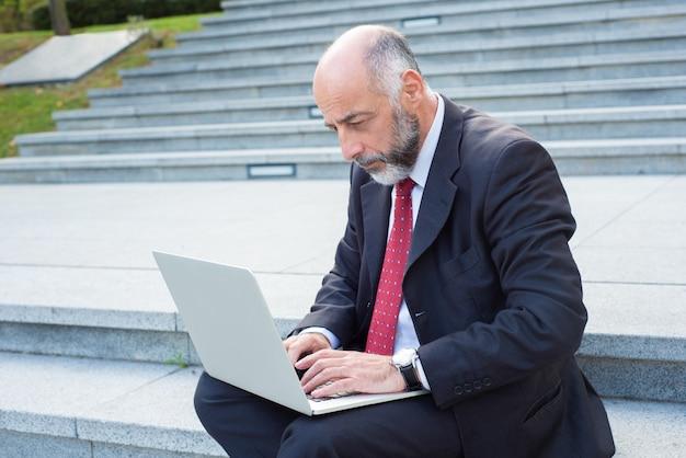 Вдумчивый бизнесмен, используя ноутбук, сидя на лестнице