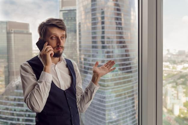 ひげを生やした思いやりのあるビジネスマンは、白いシャツとベストでモスクワの電話で話しているオフィスの窓の横に立っています