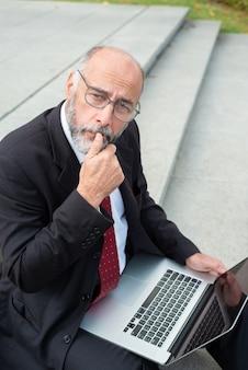 Вдумчивый бизнесмен с ноутбуком, держа руку на подбородке