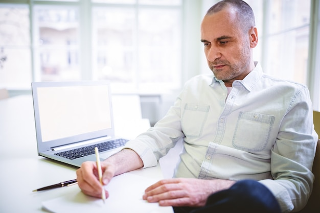 Thoughtful businessman writing document
