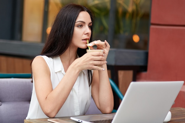 Thoughtful businesswoman has coffee break in outdoor cafeteria, uses laptop computer for distant work, waits for call on smart phone, has concentrated loook into distance, thinks about something
