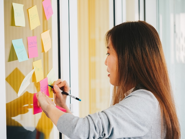 Thoughtful businesswoman looking at sticky notes thinking on glass wall