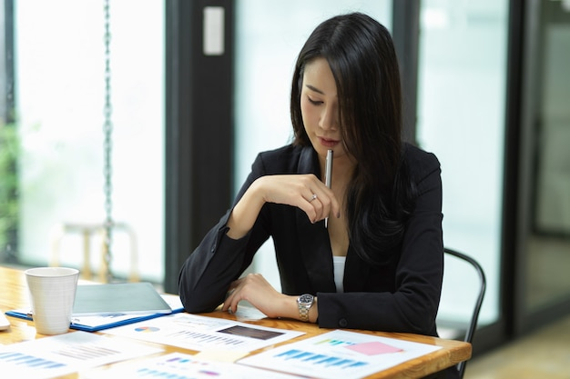 Thoughtful businesswoman thinking idea to solve business problem with financial report