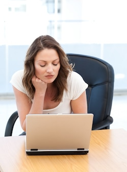 Thoughtful businesswoman working on laptop at a table