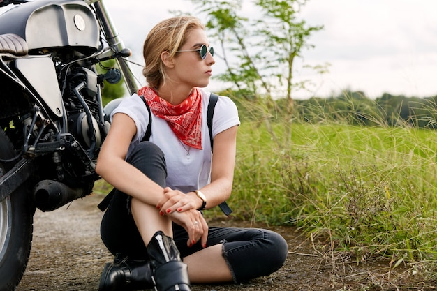 Thoughtful carefree relaxed female biker wears stylish shades, white t shirt and jeans, sits on asphalt near motorbike, being deep in thoughts. young woman looks into distance, rests after ride
