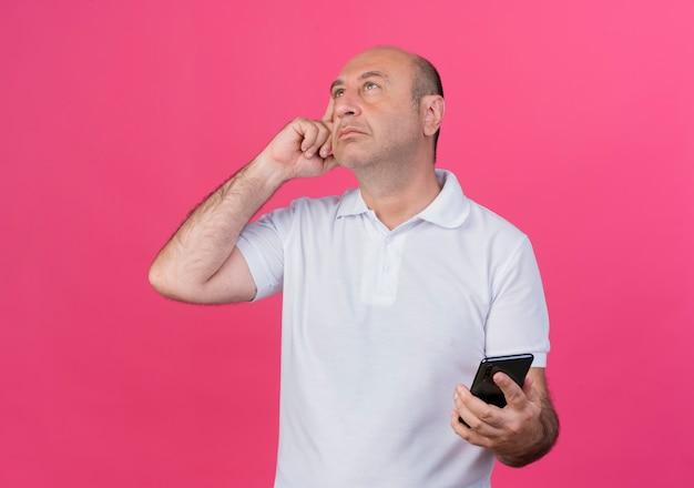 Uomo d'affari maturo casuale premuroso che osserva in su mantenendo il dito sul tempio e tenendo il telefono cellulare isolato su sfondo rosa