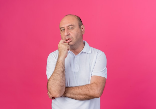 Thoughtful casual mature businessman standing with closed posture and putting finger on lip isolated on pink background with copy space
