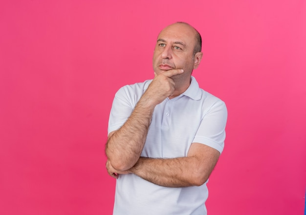 Considerato casual uomo d'affari maturo in piedi con la postura chiusa mettendo la mano sul mento guardando a lato