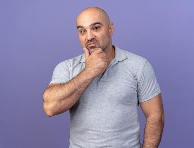 紫の壁に隔離されたあごに手を保つ思いやりのあるカジュアルな中年男性