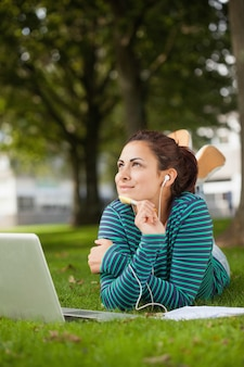 Thoughtful casual student lying on grass taking notes