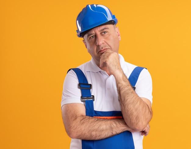 L'uomo adulto caucasico premuroso del costruttore in uniforme tiene il mento che esamina il lato sull'arancio