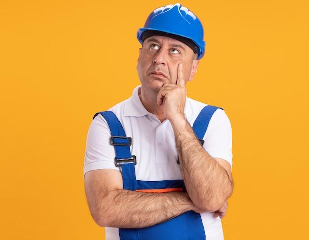 L'uomo adulto caucasico premuroso del costruttore in uniforme mette la mano sul mento e alza lo sguardo sull'arancia