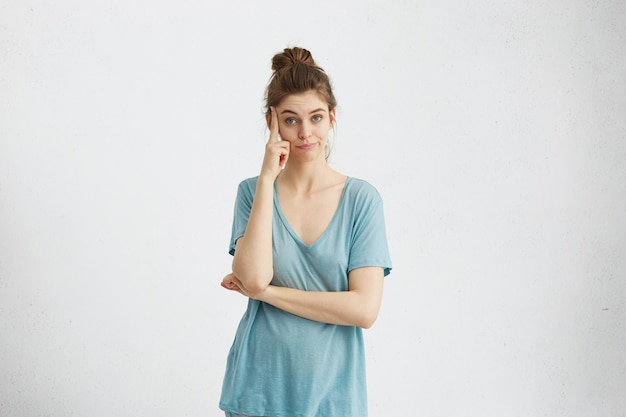 思慮深い白人女性が寺院でカジュアルな青いtシャツの指を持ち、物思いに沈んだ表情を混乱させ、熟考し、提案の賛否両論を比較検討している