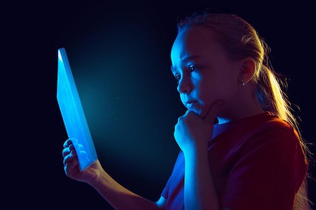인정 있는. 네온 불빛에 어두운 스튜디오 배경에 백인 여자의 초상화. 태블릿을 사용하는 아름다운 여성 모델.