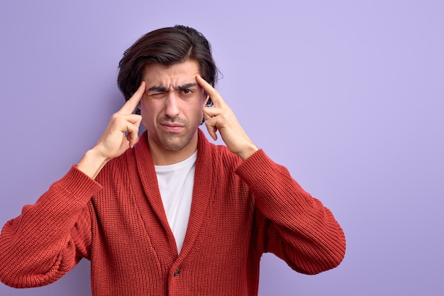 Задумчивый кавказский парень пытается вспомнить, что-то держит пальцы на виске