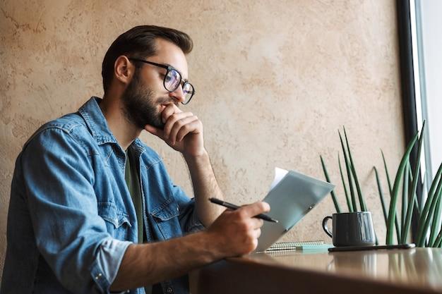 Вдумчивый кавказский мужчина в очках читает документы и пьет кофе во время работы в кафе в помещении