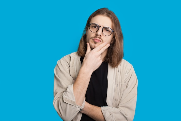 Thoughtful caucasian man with long hair and beard is looking through eyeglasses and touching his chin while posing on a blue wall