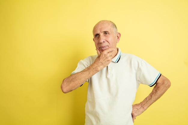 Premuroso. ritratto dell'uomo maggiore caucasico isolato su sfondo giallo studio. bellissimo modello emotivo maschile. concetto di emozioni umane, espressione facciale, vendite, benessere, annuncio. copyspace.