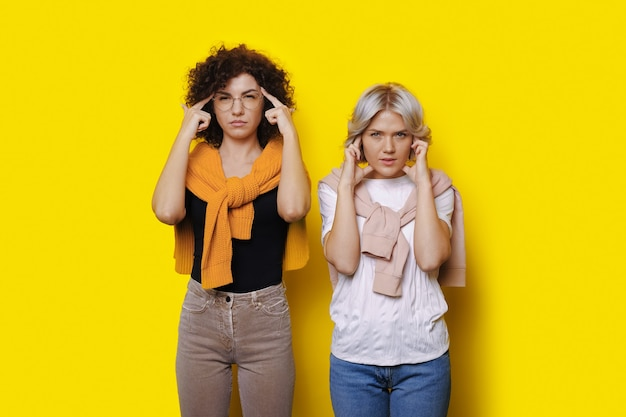 Thoughtful caucasian women with curly hair are posing on a yellow wall touching her head