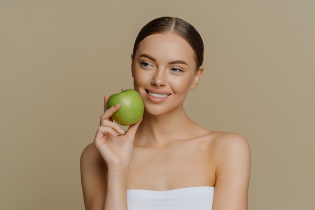 Thoughtful charming european woman holds apple near face smiles gently has white perfect teeth healthy clean skin wrapped in shower towel stands with bare shoulders