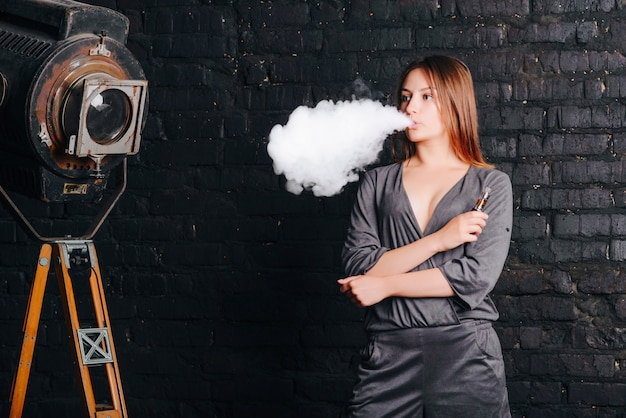 Вдумчивая очаровательная девушка курит электронную сигарету, облако дыма, фотосъемку в студии со старой камерой и кирпичной стеной. женщина, одетая в стильный костюм