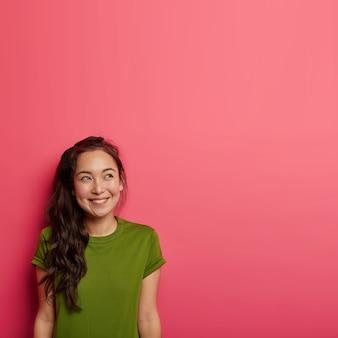 上に焦点を当てた思いやりのある陽気なアジアの女性は、緑のカジュアルなtシャツを着て、バラ色の壁を越えてポーズをとって、楽しい考えを持っています