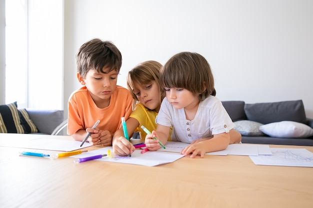 Thoughtful children painting with markers in living room. caucasian lovely boys and blonde girl sitting at table, drawing on paper and playing together. childhood, creativity and weekend concept