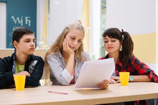 Задумчивые одноклассники с бумагами
