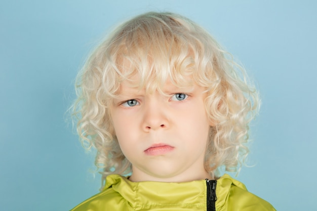 Thoughtful. close up portrait of beautiful caucasian little boy isolated on blue  wall. blonde curly male model. concept of facial expression, human emotions, childhood,