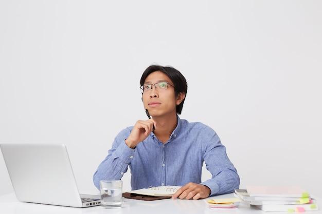 白い壁に隔離されたテーブルでノートに考えて書く眼鏡の思慮深い集中アジアの若いビジネスマン