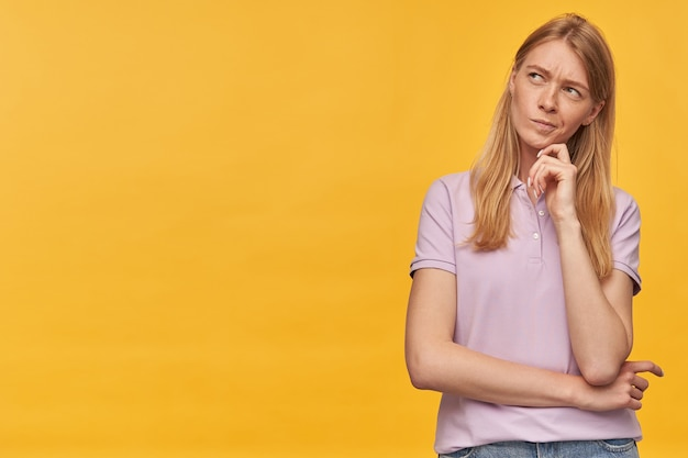 ラベンダーのtシャツにそばかすのある思いやりのある集中女性は、黄色の空きスペースを考えて横を向いています